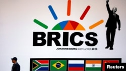 A police officer walks past a billboard outside the BRICS summit meeting in Johannesburg, South Africa, on July 25.