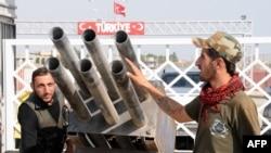 Rebeli sirieni examinînd un dispozitiv de lansare de rachete în apropiere de frontiera cu Turcia