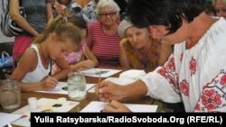 Марія Яненко проводить майстер-клас з петриківського розпису