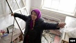 Пенсіонерка показує зруйнований будинок у Донецьку