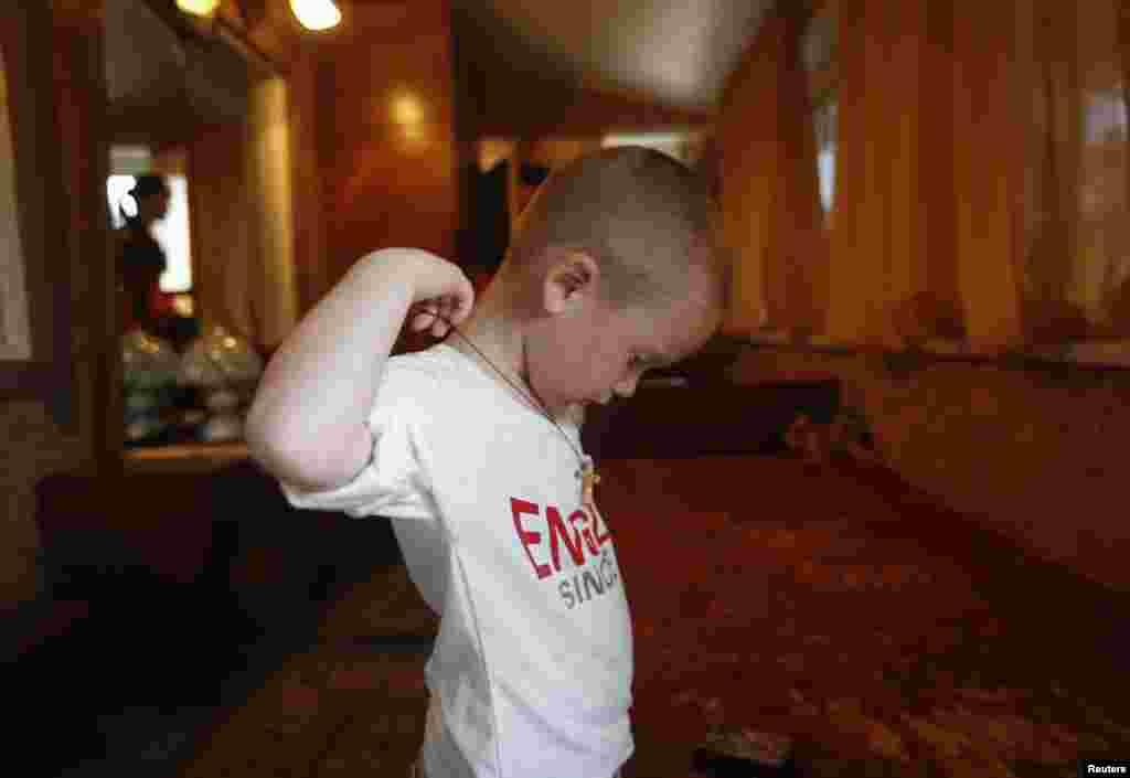 Хлопчик одягає православний хрест в тимчасовому житлі в місті Нижня Кринка