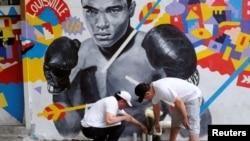 Njerëzit duke vendosur lule afër fotografisë së Muhammad Aliut më 4 qershor në Feniks të Arizonës