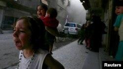 دو دختر سوری و کودکی هشت ماهه از نزدیک یک کاروان هلال احمر که در حاشیه دمشق هدف موشک قرار گرفته میگریزند