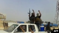 A screen grab taken from a video uploaded to YouTube on June 17 allegedly shows militants ISIL parading with their weapons in the northern Iraqi city of Baiji.