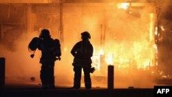 Пожарные пытаются потушить пожар в одном из подожженных зданий в Фергюсоне