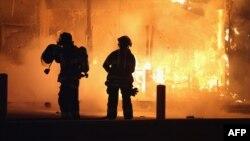 آتشنشانها در حال خاموش کردن آتش در رستورانی که هدف حمله گروهی از معترضان خشمگین قرار گرفته است