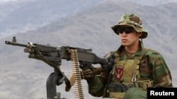 A Special Forces member from the Afghan National Army mans a machine gun on an armored vehicle while leaving for a mission with U.S. Special Forces soldiers in Kunar Province on March 12.