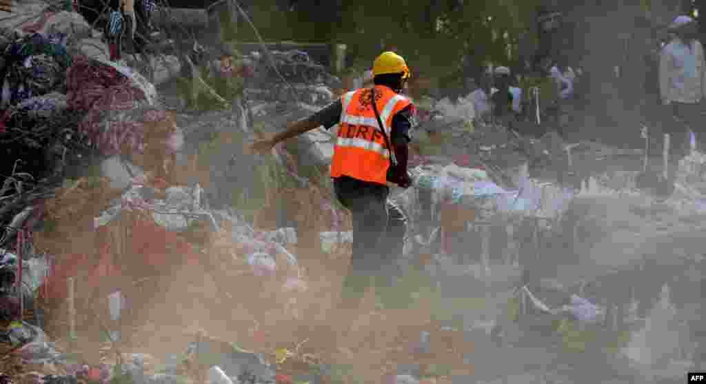 Індія – Працівник Національної служби реагування на надзвичайні ситуації на руїнах нелегально зведеного житлового будинку, що завалився на околиці міста Мумбая, 6 квітня 2013 року. На вечір цього дня число виявлених жертв сягнуло 63 і може ще зрости.