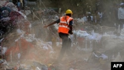 An Indian rescue worker rushes through the rubble and debris at the site of a building collapse on the outskirts of Mumbai on April 6.