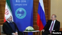 Iranian President Hassan Rouhani (L) meets with Russian President Vladimir Putin on the sidelines of the Shanghai Cooperation Organisation Summit (SCO) in Qingdao, China June 9, 2018. Mikhail Klimentyev/Kremlin REUTERS