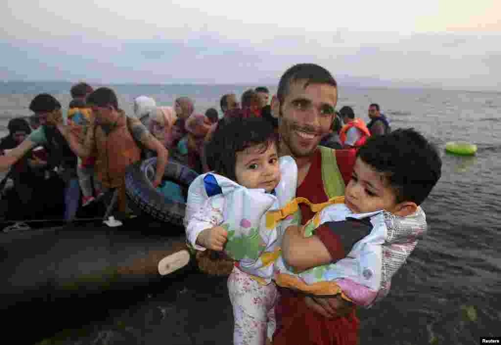 "A Syrian refugee from Kobani holds two children as he jumps off a small boat onto a beach on the Greek island of Kos after crossing the Aegean Sea from Turkey. The UNHCR called on Greece to take control of the ""total chaos"" on its Mediterranean islands, where thousands of migrants have landed. About 124,000 have arrived this year by sea, many via Turkey. (Reuters/Yannis Behrakis)"