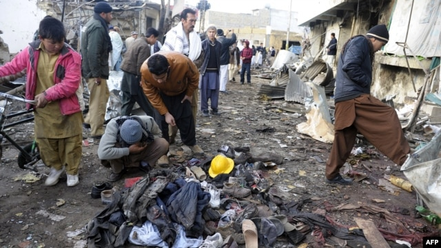 Local residents look at clothes left in a pile at the site of overnight twin suicide bombings in Quetta on January 10.
