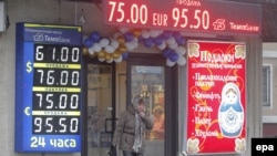 A woman walks in front of electronic information panels displaying currency exchange rates in Moscow on December 17.