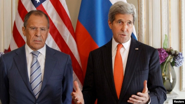 France -- U.S. Secretary of State John Kerry (R) gestures as he stands with his Russian counterpart Sergey Lavrov, before their meeting in Paris, June 5, 2014.