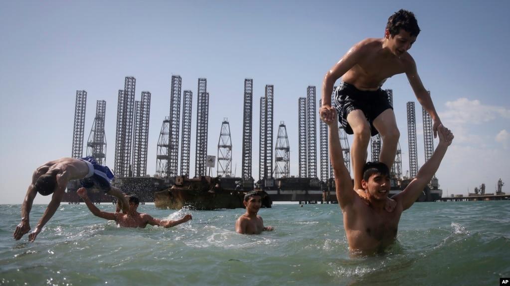 Каспий теңізінің Бакудегі жағалауында мұнай платформасы алдында шомылып жүрген балалар.