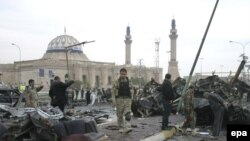 Iraqi soldiers inspect the site of one of the car-bomb attacks, in the Al-Qahira neighborhood of Baghdad, on December 8.