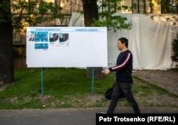 Қазақстан президенттігіне кандидаттардың сайлау жарнамаларының қасынан өтіп бара жатқан адам. Алматы, 13 мамыр 2019 жыл.