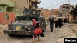 Іракські біженці залишають небезпечний район під час зіткнень між іракськими військовими і бойовиками угруповання «Ісламська держава» у західному Мосулі, 16 травня 2017 року