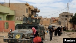Displaced residents flee during clashes between Iraqi forces and Islamic State militants in western Mosul on May 16.