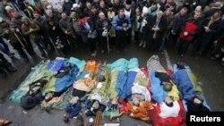 Ուկրաինացի ցուցարարները աղոթում են զոհվածների դիակների մոտ, Կիև, 20-ը փետրվարի, 2014թ․