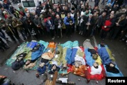 Қаза тапқан шерушілерге қарап тұрған демонстранттар. Киев, 20 ақпан 2014 жыл.