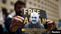 Участник демонстрации в Тбилиси держит плакат с призывом освободить азербайджанского журналиста Афгана Мухтарлы, похищенного из Грузии. 31 мая 2017 года.