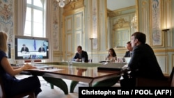France - French President Emmanuel Macron (R), and flanked by his delegation, speaks during a visio conference with Kosovo Prime Minister Avdullah Hoti, Serbian President Aleksandar Vucic, and German Chancellor Angela Merkel, at the Elysee Palace, in Pari
