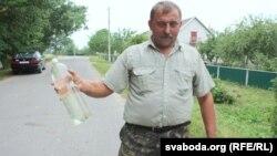 Валер Білібуха дэманструе бутэльку з жаўтаватай вадой з вадаводу