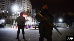 Afghan security forces block a road as they stand guard near the security perimeter set up around the Serena Hotel in downtown Kabul late overnight on March 20-21, when four gunmen killed at least nine people there.