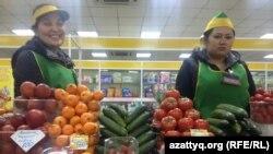 Торговцы рынка у прилавков с новыми ценниками после девальвации. Астана, 18 февраля 2014 года.