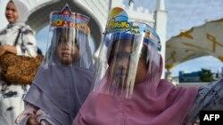 Дети в защитных масках в Индонезии, иллюстрационное фото