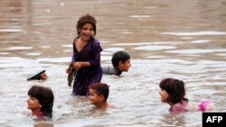 Pakistani children play in floodwaters following heavy rain in Aza Kheil, some 40 kilometers from Peshawar.