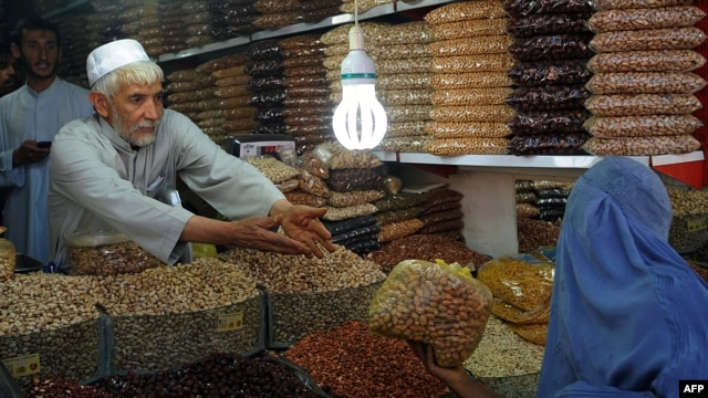A woman buys dry fruit during the month of Ramadan as Eid al-Fitr approaches in Herat.