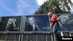 Прохожий в Гамбурге идет мимо рекламы прохладительных напитков с портретами президента Турции Эрдогана, президента РФ Владимира Путина и президента США Дональда Трампа