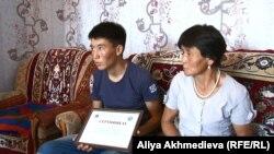 Рысбек Досан с сертификатом акима и мать юноши Тансык Уатхан. Алматинская область, 5 августа 2015 года.