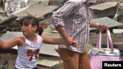 پدری دست دختر خود را گرفته و از محل موشکپرانی مخالفان در منطقه تحت کنترل دولت در حلب در حال فرار هستند