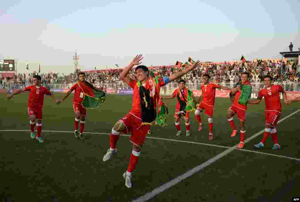 Afghan footballers celebrate their 3-0 win in a friendly against Pakistan at the Afghanistan Football Federation (AFF) stadium in Kabul. Afghanistan was hosting its first international soccer match in a decade. Organizers are hoping the FIFA-sanctioned match will ease cross-border tensions between the two neighbors. It's the first meeting in 36 years for the two nations' national soccer teams. (AFP/Massoud Hossaini)