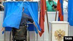 Россия - Человек в инвалидной коляске в кабине для голосования во время процедуры голосования, репетиция декабрьских выборов в Думу на экспериментальном участке в Центральной избирательной комиссии. 7 августа 2007г.