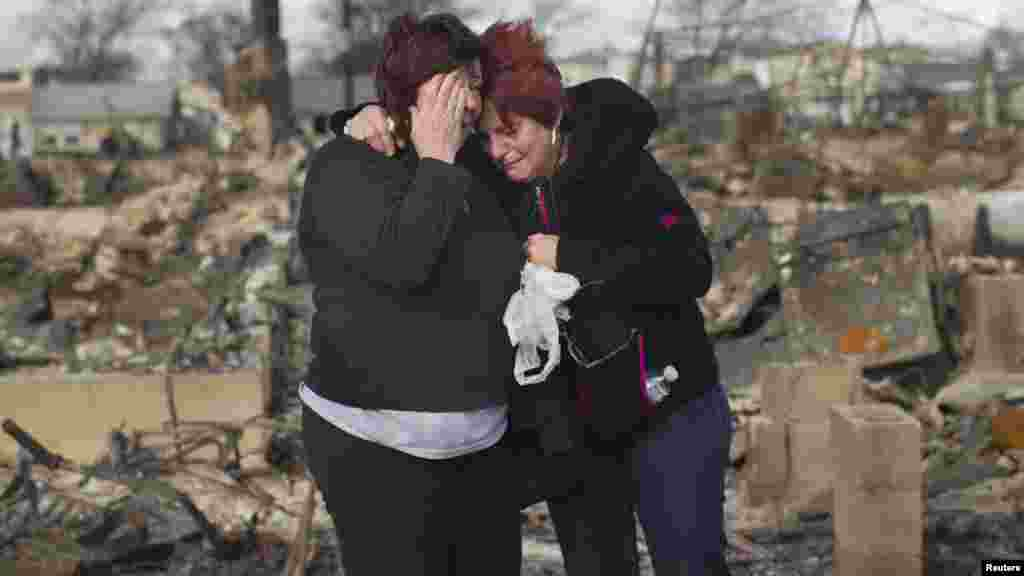 Neighbors Lucille Dwyer (right) and Linda Strong embrace after looking through the wreckage of their homes in the aftermath of Hurricane Sandy in the Breezy Point section of the Queens borough of New York. (Reuters/Shannon Stapleton)