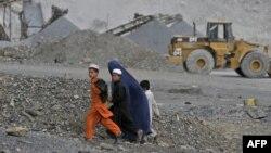 Ауған әйел балаларымен Турхам кен орнының қасынан өтіп барады. Нангархар, 5 қазан 2011 жыл