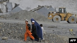 A family walks near an open cast mine in the Nangarhar region of eastern Afghanistan.