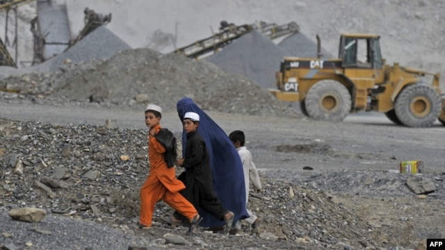 An Afghan woman and her children walk near an open-cast mine in the Turkham Nangarhar region of Afghanistan bordering Pakistan. Manufacturing, mining, and Afghanistan's agricultural sectors would be the most likely areas of investment.