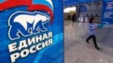 RUSSIA -- A woman walks past United Russia political party sign during the party's annual convention in Moscow, Russia December 8, 2018