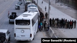 Rebel fighters are evacuated from the city of Harasta in the eastern Damascus suburb of Ghouta on March 22.