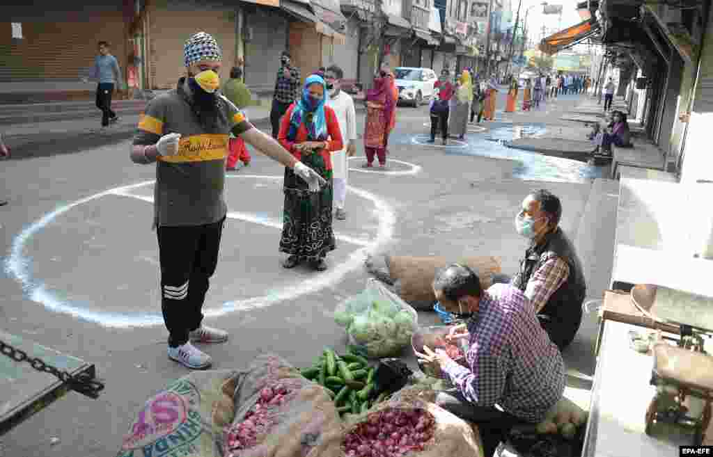 People in the Indian city of Jalandhar stand on designated areas to maintain social distancing as they wait to buy vegetables.