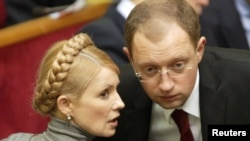 Then-Foreign Minister Arseniy Yatsenyuk chats with Yulia Tymoshenko in the Ukrainian parliament in Kyiv in 2007.