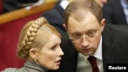 Then-Foreign Minister Arseniy Yatsenyuk chats with Yulia Tymoshenko in the Ukrainian parliament in Kyiv in 2007.