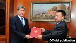 Recently sworn-in President Almazbek Atambaev (left) delivers the mandate for forming a new governing coalition to Social Democratic Party leader Chynybai Tursunbekov on December 8.