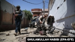 Afghan security officials inspect the scene of a bomb blast near a voter-registration center in Jalalabad on April 29.