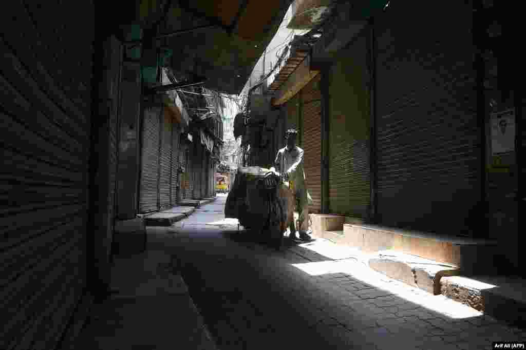 Пакістанскі вулічны прадавец праходзіць міма рынку падчас забастоўкі гандляраў супраць павышэньня цэн у Лахоры.ARIF ALI / AFP